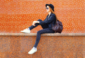 Female student sitting on wall with backpack